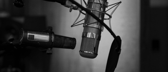 Black and white image of microphone in a recording studio in front of a grey wall.
