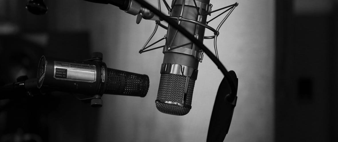 Schwarz-Weiß-Bild von Mikrofon im Aufnahmestudio vor einer grauen Wand.