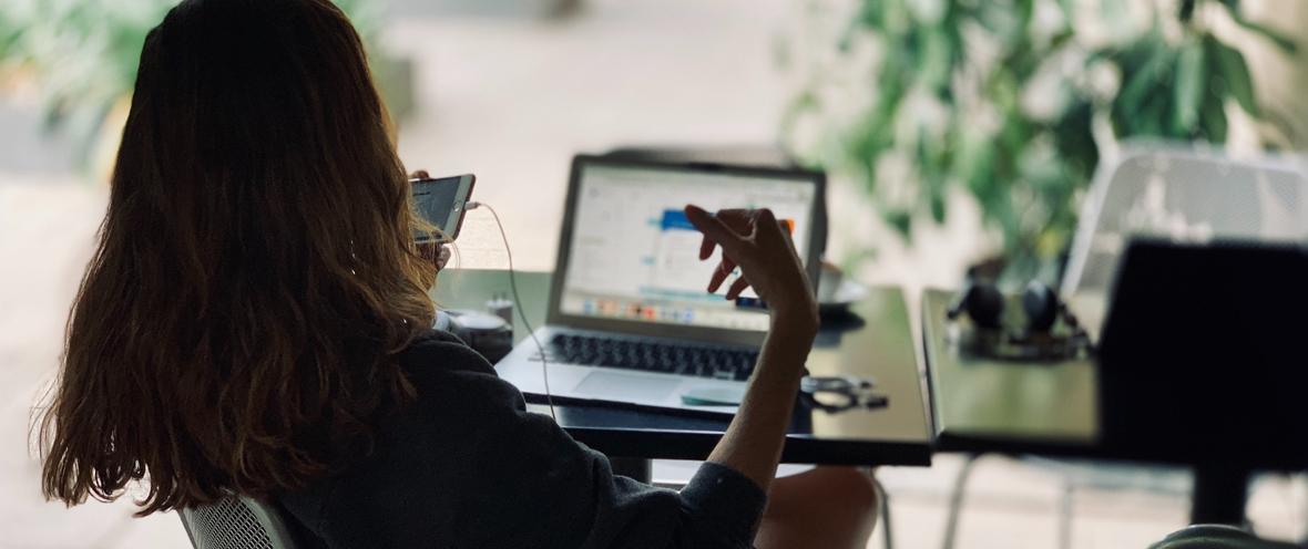 Frau sitz vor einem Tisch mit Laptop und Smartphone in der Hand.