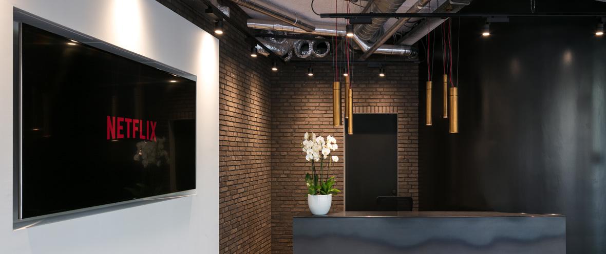 Büro mit Empfangsbereich mit Hängeleuchten und Monitor mit Netflix-Logo