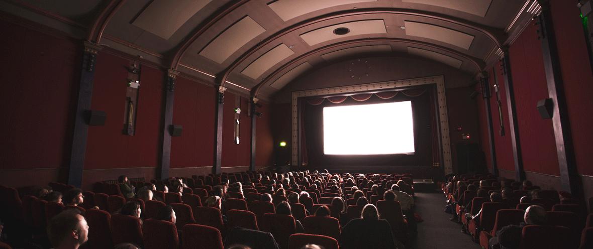Mit Menschen besetzter Kinosaal vor einer weißen Kinoleinwand.
