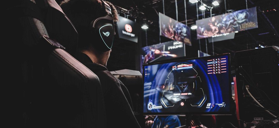 Computerspieler auf einer Messe vor einem Bildschirm.