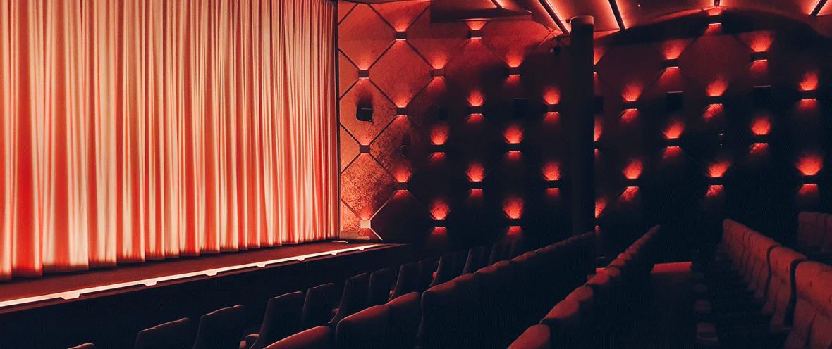 Kinosaal mit Sitzen und Bühne mit roten Lichtern beleuchtet.