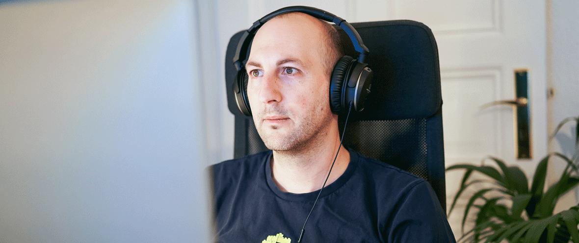 Bild von Claudius Urban mit Kopfhörern vor einem Computerbildschirm.