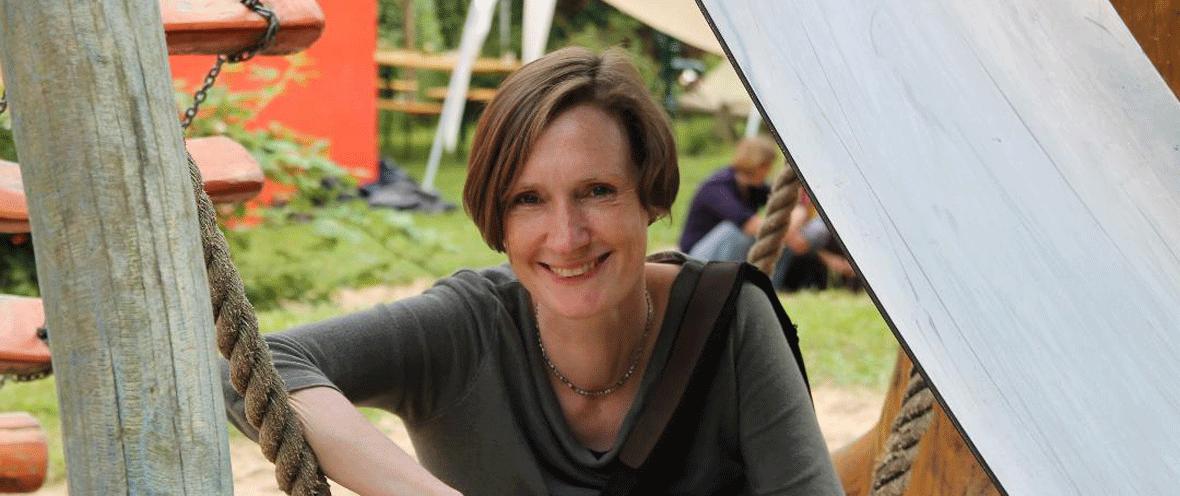 Anke Oxenfarth, Leiterin der Stabsstelle Nachhaltigkeit des Oekom-Verlages im Freien mit Personen im Hintergrund