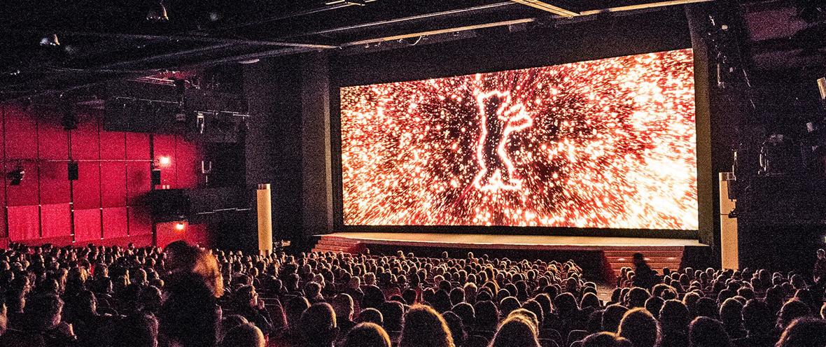 Berlinale-Bär auf einer Kinoleinwand vor einem sitzenden Publikum.